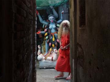 A sadhu walks past a clay idol of Goddess Kali, the goddess of power in Dhami